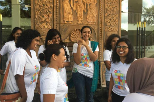 """A group of young women smiling and laughing wearing shirts reading """"Write to Reconcile"""""""