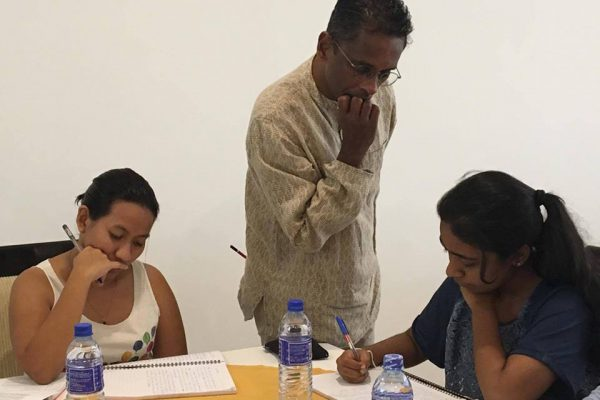 Two seated young women write in notepads while a man stands over them observing their writing.