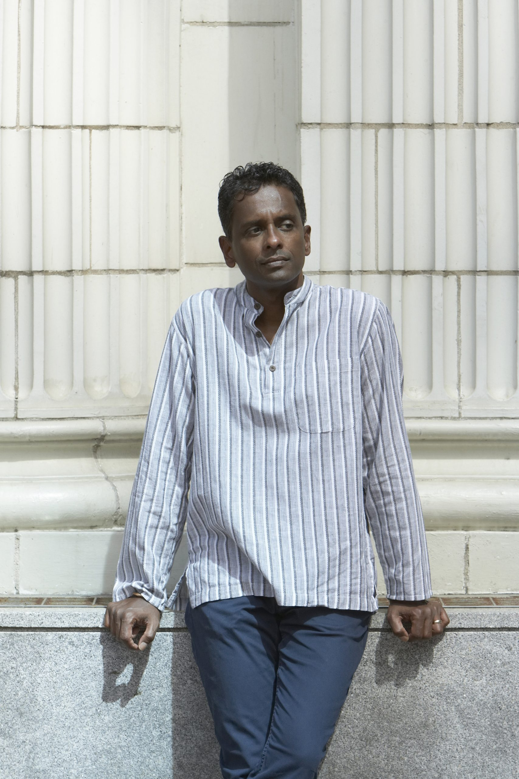 Portrait of author Shyam Selvadurai leaning against an ivory coloured wall in a striped shirt.