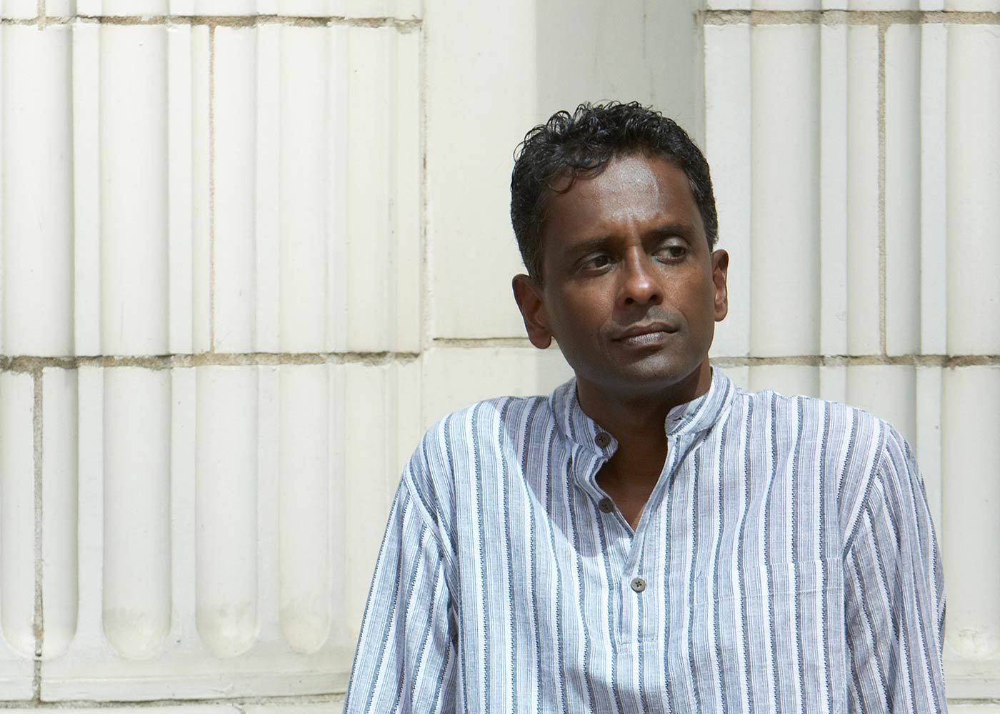 Portrait of author Shyam Selvadurai leaning against wall by Kevin Kelly