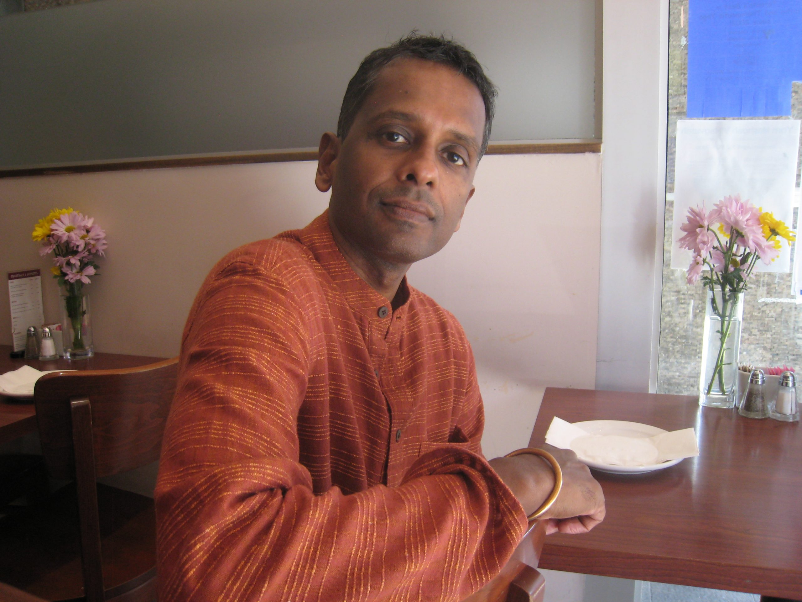 Portrait of author Shyam Selvadurai sitting at a table in a restaurant.